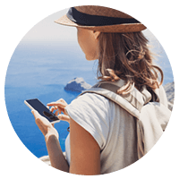 Female tourist on mobile device in front of ocean