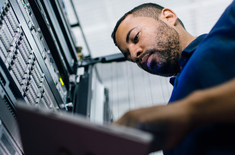 IT network administrator reviewing business data from hyperconverged virtual machine in data center