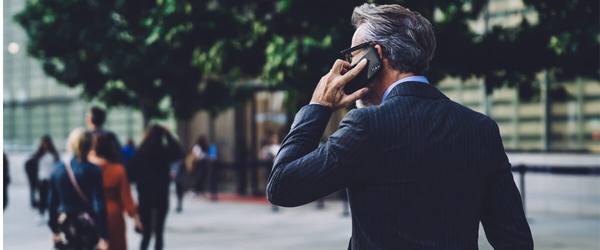 Business man speaking on phone outside