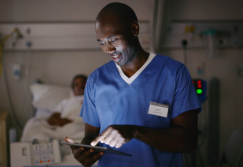 Smiling nurse gives check up to male patient while holding tablet device. Shop Healthcare contracts, Shop GPO contracts, Shop Premier contract, Shop Vizient contract, Shop HealthTrust contract, Shop Intalere cntract